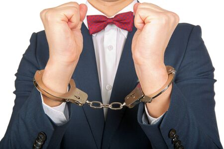 handcuffed hands: Close up photo of a handcuffed businessman hands