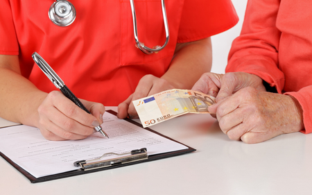 paying money: Senior woman paying money for medical service Stock Photo
