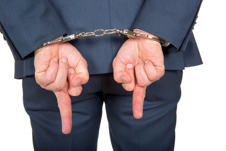 handcuffed: Close up photo of a handcuffed businessman hands