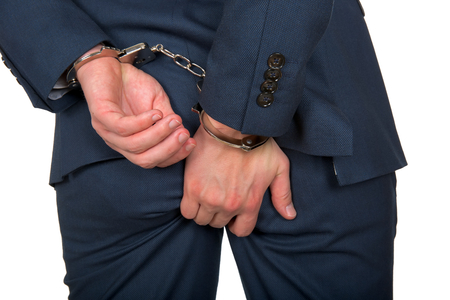 Close up photo of a handcuffed businessman hands