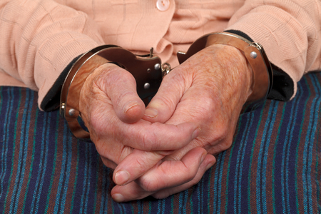 handcuffed: Close up photo of a handcuffed elderly woman