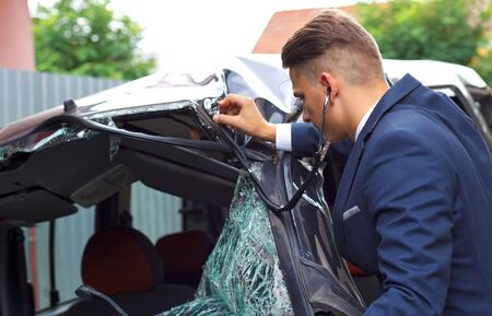 drunk test: Well dressed insurance assessor inspecting damaged vehicle with a stethoscope Stock Photo