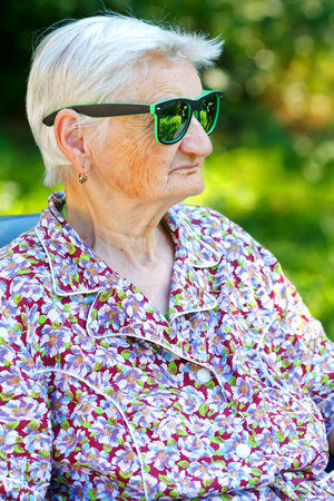 Photo of a senior woman wearing trendy sunglasses