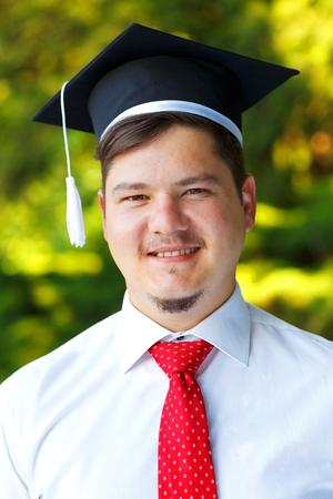 Glückliche graduateing Schüler tragen Graduierung Hut