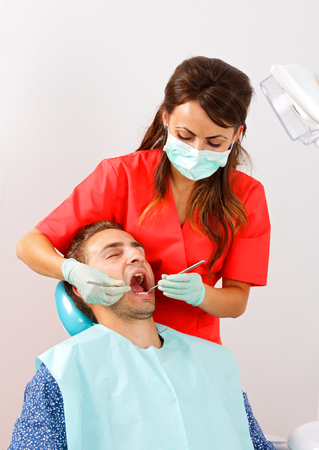 dental calculus: The dentist is checking the patients mouth