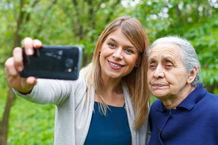 comunication: Picture of a beautiful young woman taking selfies woth her grandmother Stock Photo