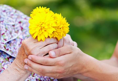 soledad: Hombre joven que da una flor amarilla de la mujer mayor