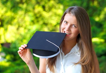 Foto von einer wunderschönen jungen Frau glücklich Blick auf ihre Graduierung Kappe