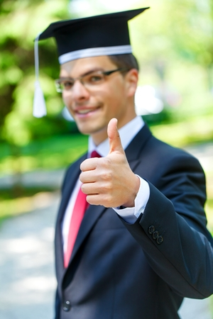 Glückliche graduateing Student Abschluss-Hut trägt ans Daumen nach oben