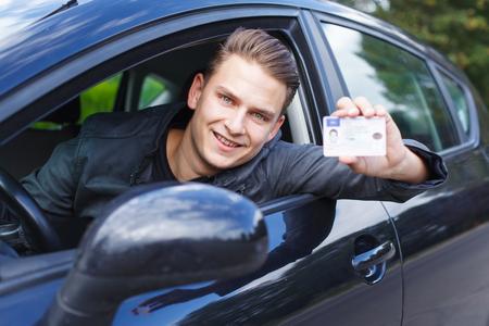 Portret van een knappe jonge man besturen van een auto Stockfoto