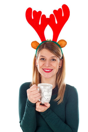 Picture of a smiling young woman with raindeer slide holding a cup of tea Stock Photo