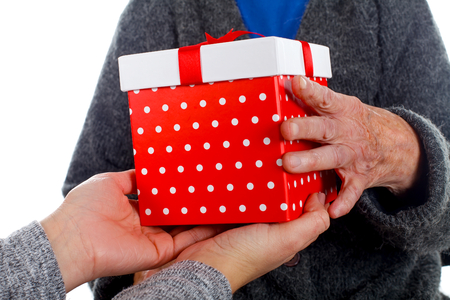 Close up picture of an aged woman receiving Christmas present from her granddaughter Stock Photo