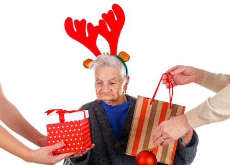 Picture of an old lady receiving Christmas gifts from the family Stock Photo