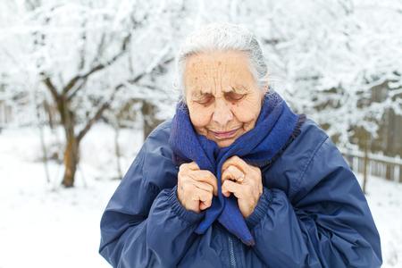 Beeld van een oude dame die koud op wintertijd voelt Stockfoto