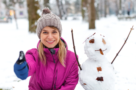 Picture of a beautiful girl posing next to a snowman