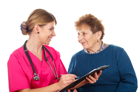 Picture of a smiling physician filling insurance papers for her patient Stock Photo