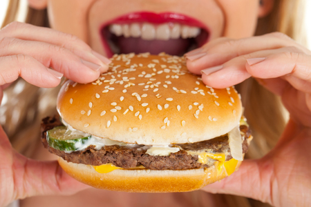 Picture of a young woman eating a delicious hamburger