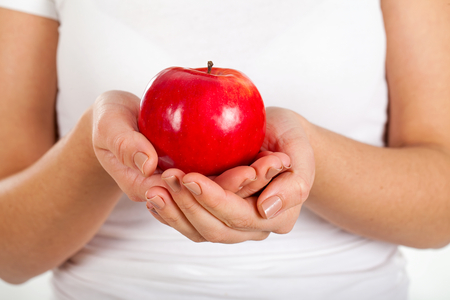 Close up picture of a fresh red apple in a womans hands