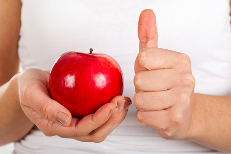 Close up picture of a fresh red apple and a woman showing thumbs up