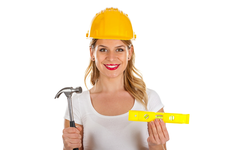 claw hammer: Picture of a confident sexy engineer holding a hammer and a spirit-level Stock Photo