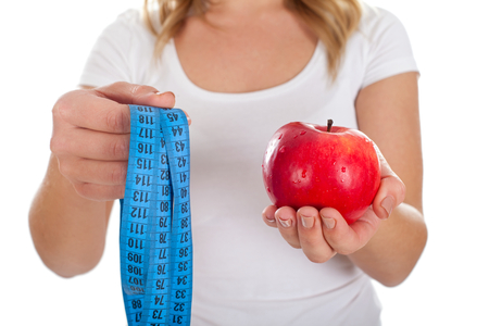 Close up picture of a woman holding measurer and a fresh apple in her hands Stock Photo