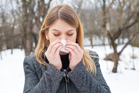 Picture of a sick young woman blowing her nose outdoor