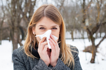 blowing nose: Picture of a sick young woman blowing her nose outdoor