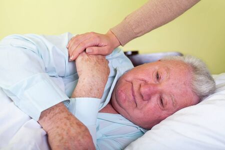 Picture of a depressed old man in bed with his caregiver Stock Photo