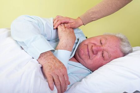 Picture of a sick elderly man in bed with his caregiver Stock Photo