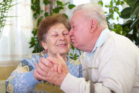 집에서 키스하는 쾌활한 노인 부부의 그림