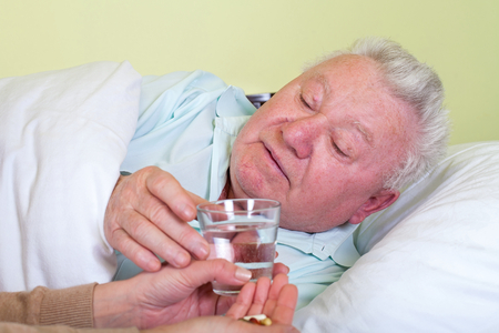 Picture of a sick old man in bed, his caregiver giving him medicine Stock Photo