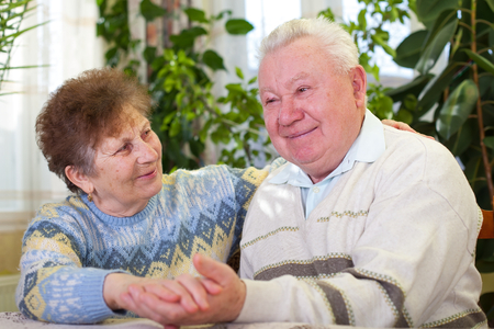 Picture of a lovely senior couple holding hands at home