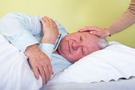 Picture of an agonized elderly man in bed