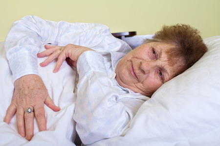 Picture of a sick elderly woman lying in bed