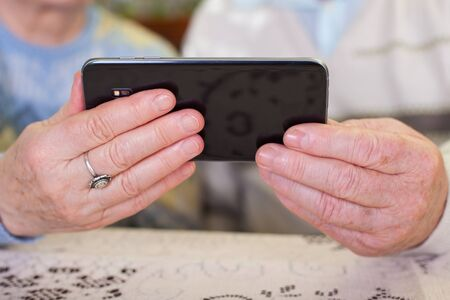 Close up picture of a senior couples hands holding a smartphone Stock Photo