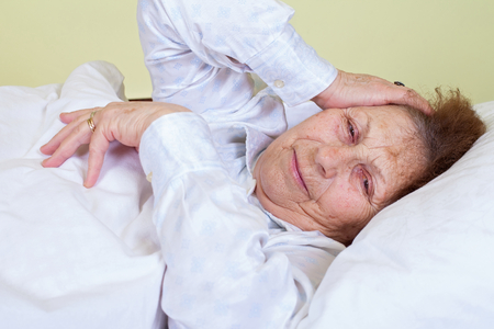 Picture of an elderly woman having a migraine, lying in bed Stock Photo