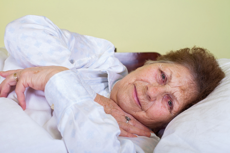 Picture of a sick old lady in bed at home
