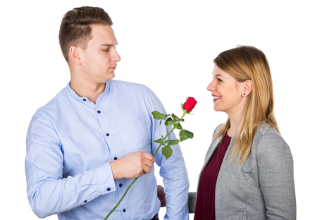 Picture of an arrogant young guy giving a red rose to his girlfriend