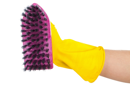 Close up picture of a purple cleaning brush held by a woman wearing yellow gloves Stock Photo