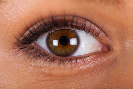 Extreme close up picture of a beautiful female hazel eye wearing natural make up Stok Fotoğraf