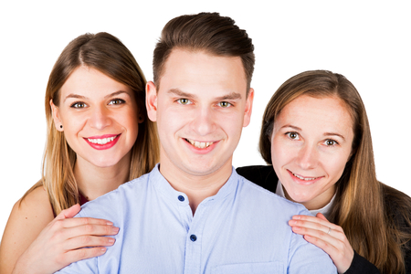Picture of two gorgeous young woman hugging a nice guy on an isolated background Stock Photo