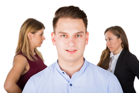 Portrait of a stressed young guy, two jealous women fighting in the background