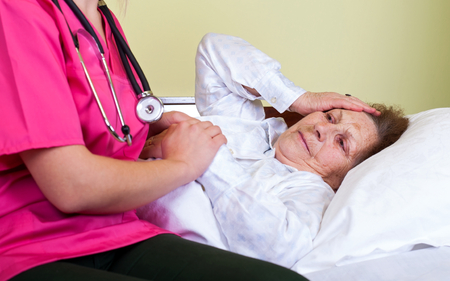 Picture of a bedridden old woman at home with her carer Stock Photo