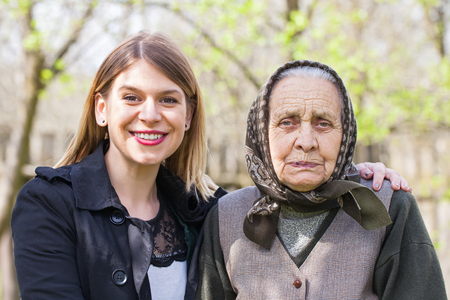 Picture of a sick elderly woman posing with her happy caretaker outdoor Stock Photo