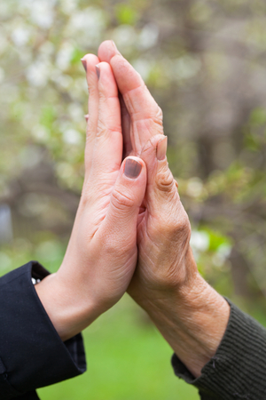 Close up picture of a young womans hands holding an elderly females hands