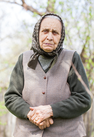 Portrait of a senior lady wearing a headscarf, posing in the garden in springtime Stock Photo