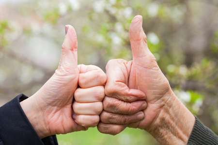 Close up picture of a senior and a young female's hand showing thumbs up outdoor