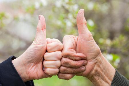 Sluit omhoog beeld van de hand van een oudste en van een jonge vrouw die duimen tonen omhoog openlucht