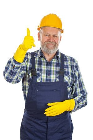 Picture of an elderly plumber wearing yellow helmet and gloves, showing thumbs up