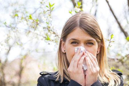 alergenos: Mujer joven con síntomas de alergia, estornudos, soplando la nariz, la primavera